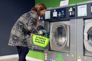 A woman washing clothes in a public Laundromat.