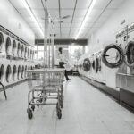 A Laundromat with a lot of washing machines that allow more clothes to be washed simultaneously, one of the main differences in doing laundry vs. laundry services.