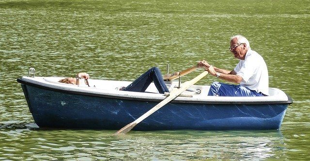 An elderly couple in a boat on a lake.