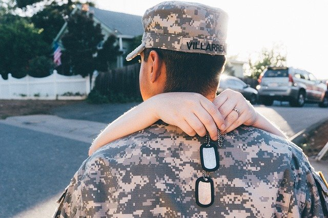 A man in a uniform hugging with his wife.