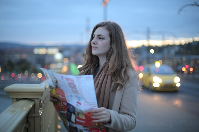 A girl on the bridge looking at a student's guide to living in Durham.